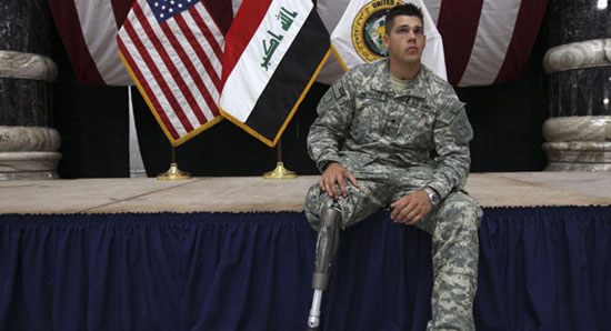 A US soldier with a prosthetic leg sits on the stage as he attends a ceremony for US soldiers who sustained combat injuries in Iraq in Baghdad